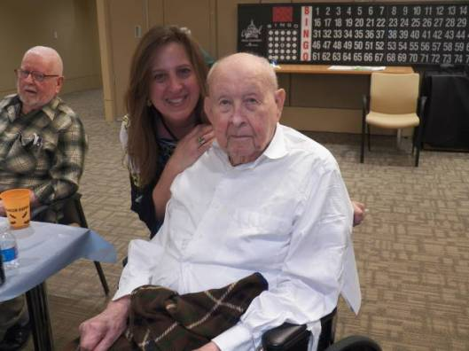 Armed Forces Retirement Home staffer Carol Mitchell helps resident Martin Tobiessen celebrate his birthday at Happy Hour on March 26 at the Home.