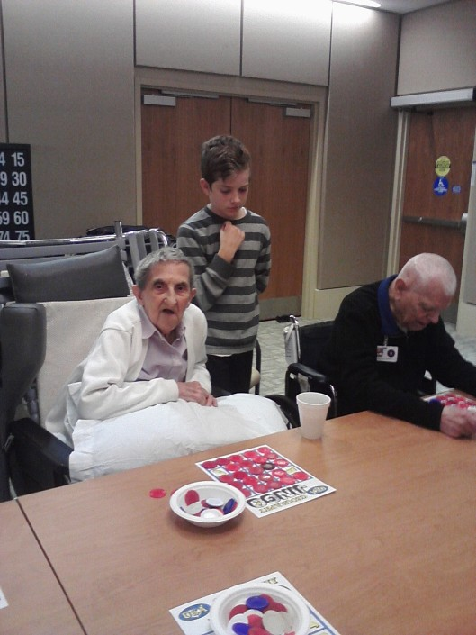 Veteran Margaret Tuck, left, has sharp eyes to go along with her sharp mind, but she has trouble hearing the Jingo calls. With Friends volunteer Teddy Hughes at her side, she is able to try to fill her card and collect a pot! Photo credit: Lori Lincoln.